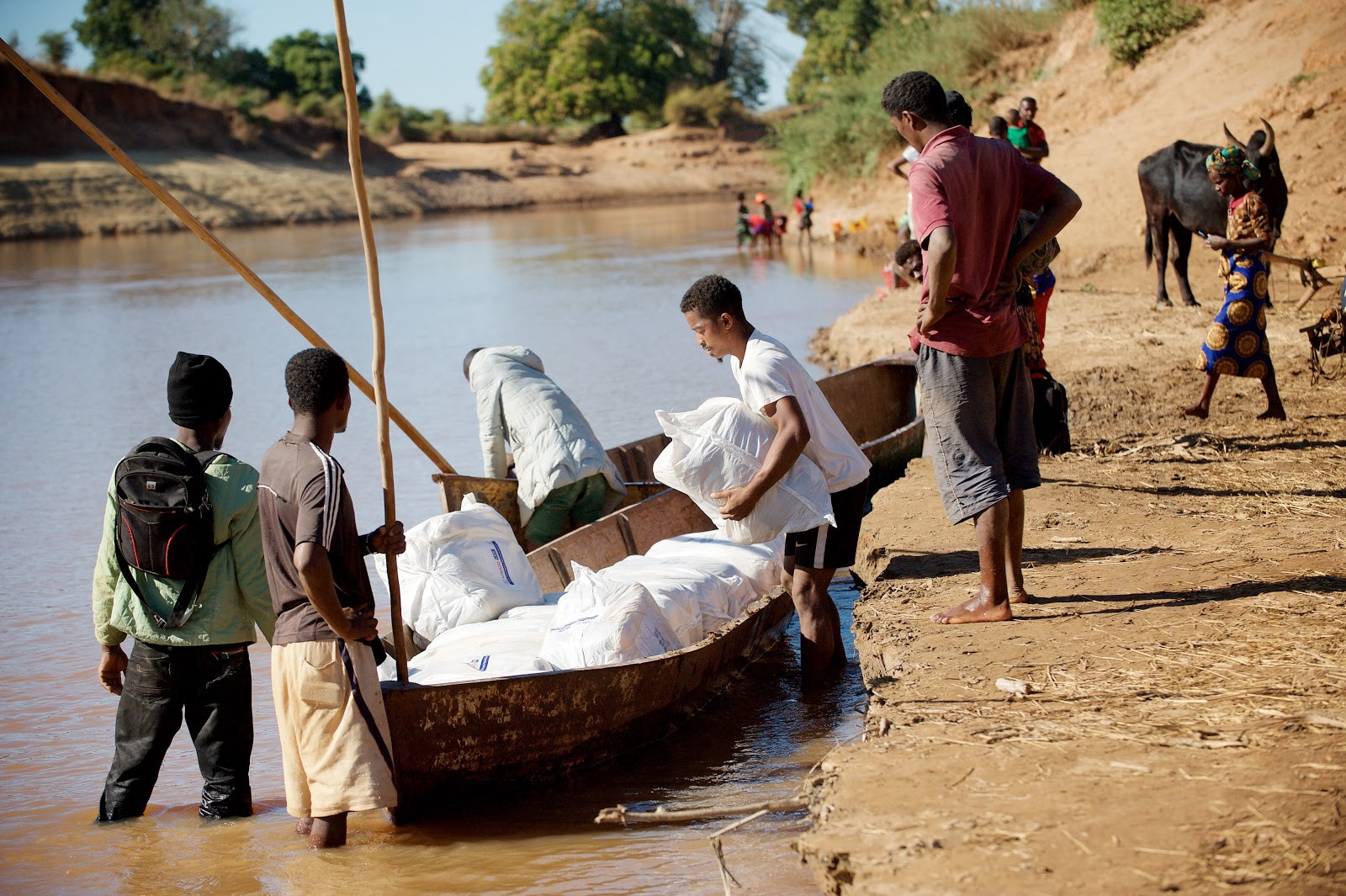 Malaria nets are placed onto pirogues to be transported across a river. / Lan Andrian, USAID Global Health Supply Chain Program — Procurement and Supply Management