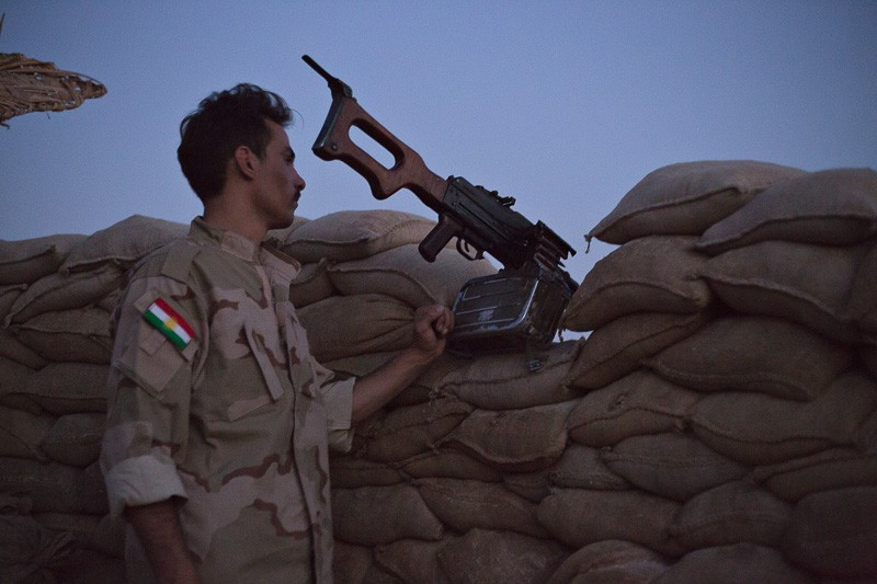 01/09/2015. Bashiqa, Iraq. An Iranian Kurdish peshmerga fighter, belonging to the PAK group, watches from the emplacement where they man a defensive line alongside Kurdish peshmerga on Bashiqa Mountain near Mosul, Iraq. Bashiqa Mountain, towering over the town of the same name, is now a heavily fortified front line. Kurdish peshmerga, having withdrawn to the mountain after the August 2014 ISIS offensive, now watch over Islamic State held territory from their sandbagged high-ground positions. Regular exchanges of fire take place between the Kurds and the Islamic militants with the occupied Iraqi city of Mosul forming the backdrop. The town of Bashiqa, a formerly mixed town that had a population of Yazidi, Kurd, Arab and Shabak, now lies empty apart from insurgents. Along with several other urban sprawls the town forms one of the gateways to Iraq's second largest city that will need to be dealt with should the Kurds be called to advance on Mosul.
