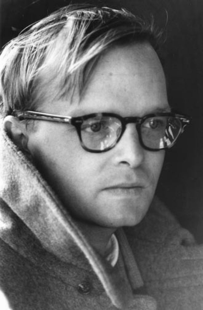 Truman Capote with glasses and a coat