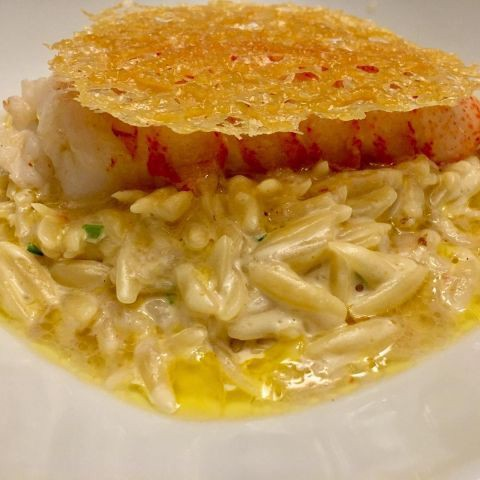 Lobster tail on orzo with a Parmesan crisp.