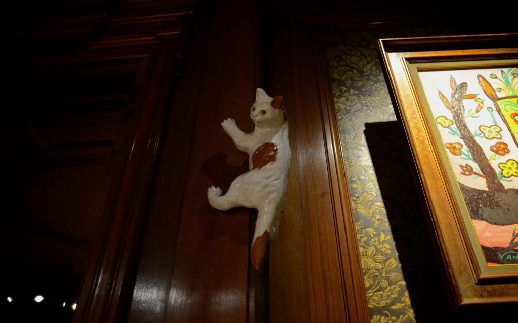 cat museum in amsterdam, porcelain cat climbing on the wall