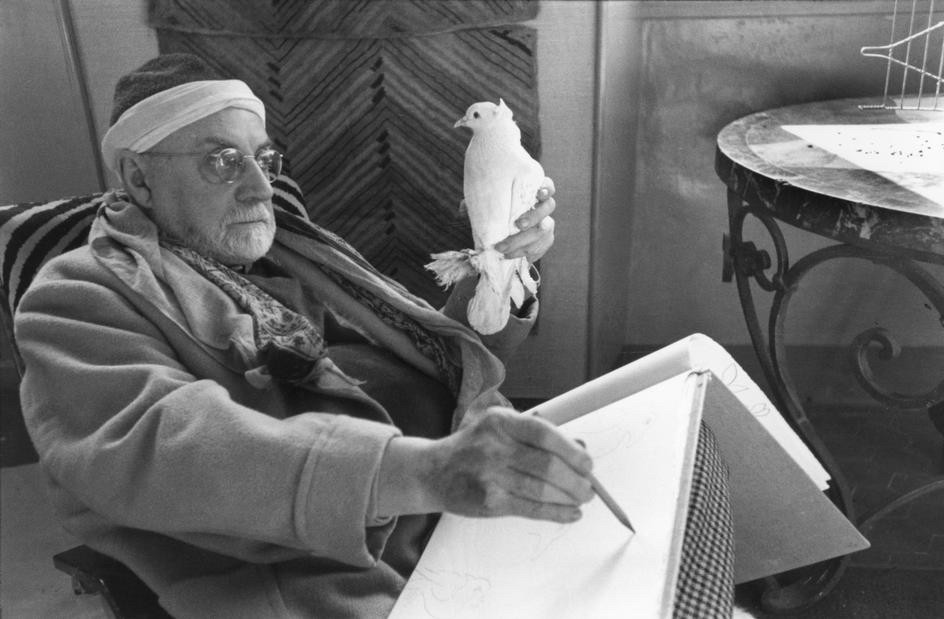 Henri Matisse holding a dove in his left hand and drawing him by the right hand