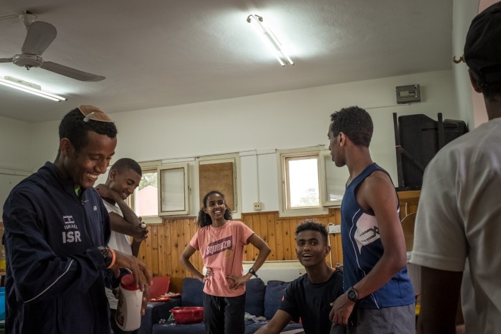 """Eritrean asylum seeker and athletes Rahel (center) and Amar (third from right) chat with their teammates during a training camp in northern Israel organized for their """"Alley Athletics"""" team where young African asylum seekers, children of Filipino migrant workers and Israeli of diverse backgrounds, spend time and practice athletics as a team."""