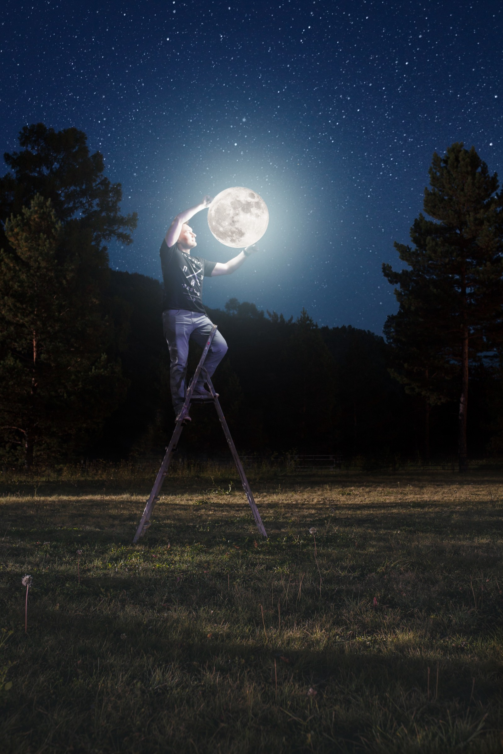 A man on a ladder poses so it appears he is holding the moon in his arms.