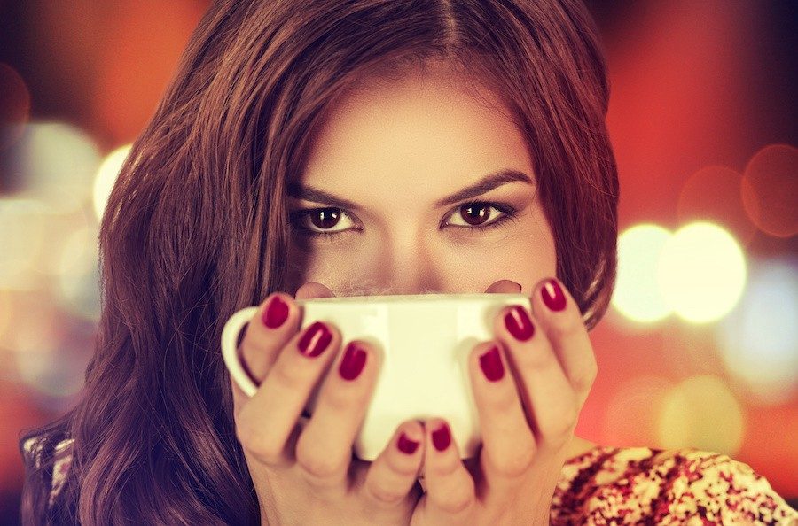 Coffee. Young beautiful Girl woman drinking Tea Cappuccino in trendy cafe shop. Beauty Model with Cup of Hot Beverage. Closeup portrait, warm colors. Human emotions positive facial expressions feeling