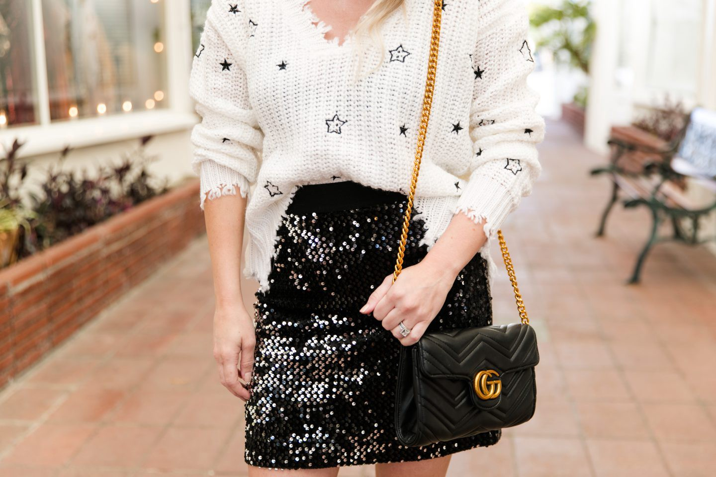 How to style a black sequin skirt in Winter featured by top Orange County fashion blog, Dress Me Blonde: image of a blonde woman wearing a 4SI3NNA star sweater, Steve Madden suede booties, Sanctuary black sequin skirt, Gucci shoulder bag, retro sunglasses,