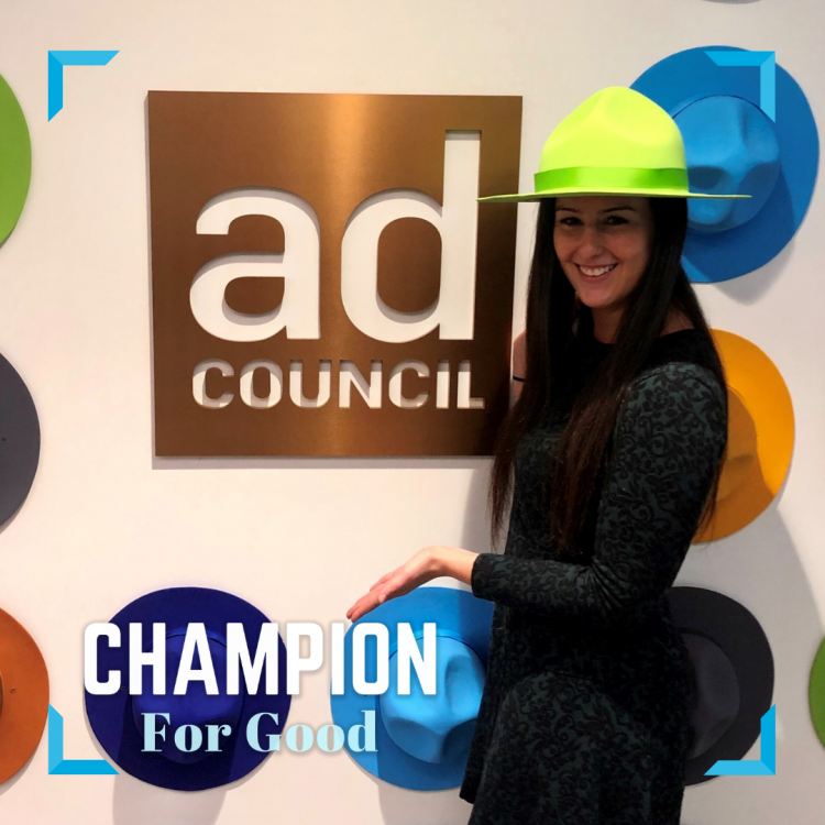 Nikki Silber wears a green Smokey Bear hat in front of a gold Ad Council sign.