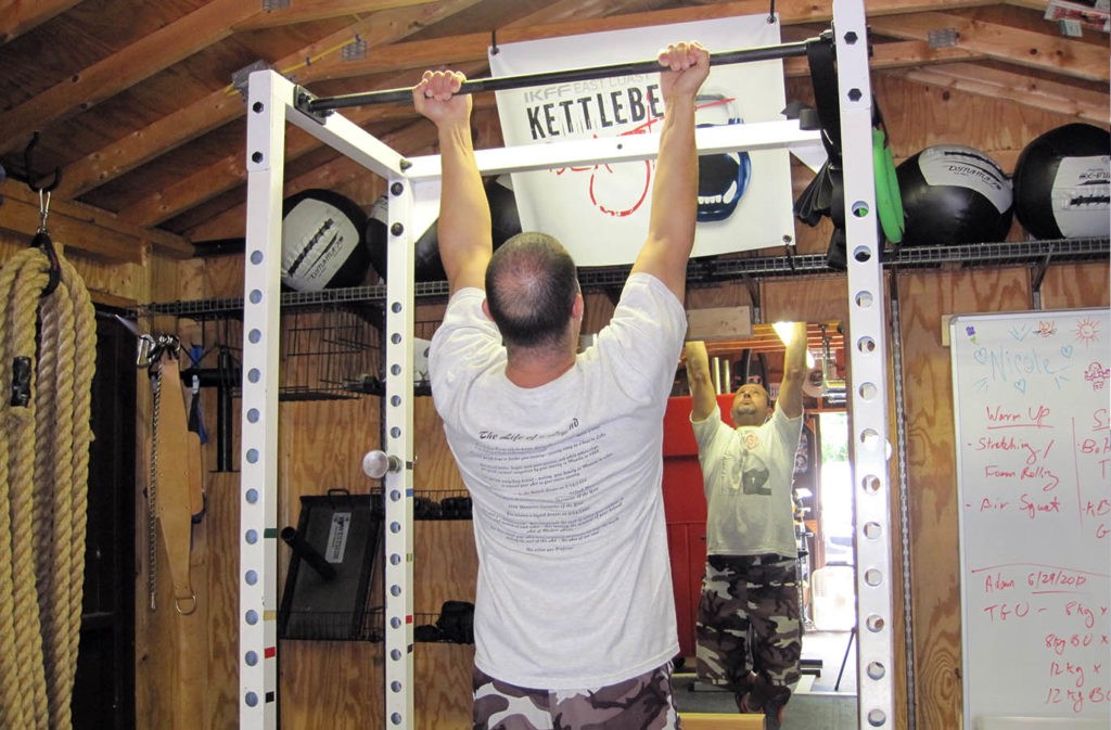 man hanging from pull up bar with finger facing toward him