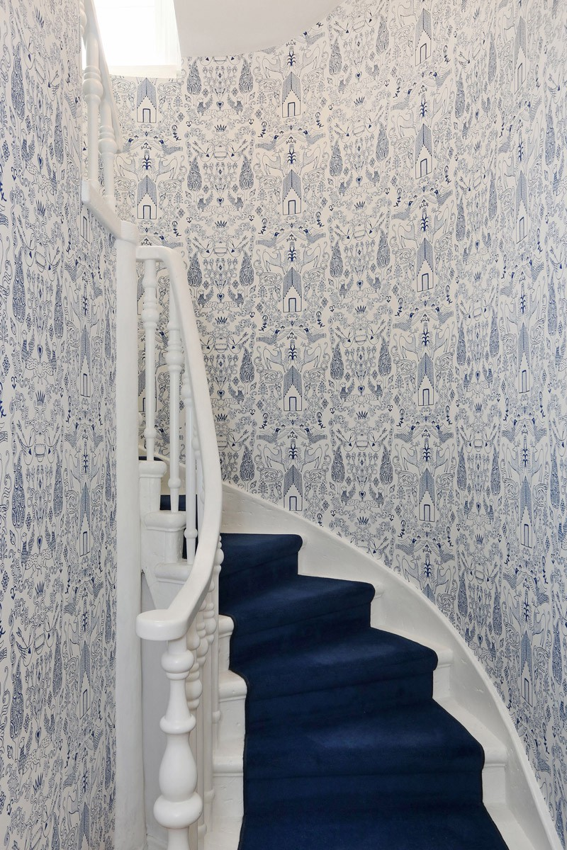 Julia Rothman's Nethercote wallpaper and a bold, blue carpet give Mimi and Brenden's staircase a colorful and cozy feel.