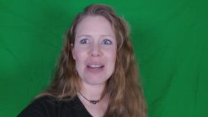 Laura looking distressed in front of green screen.
