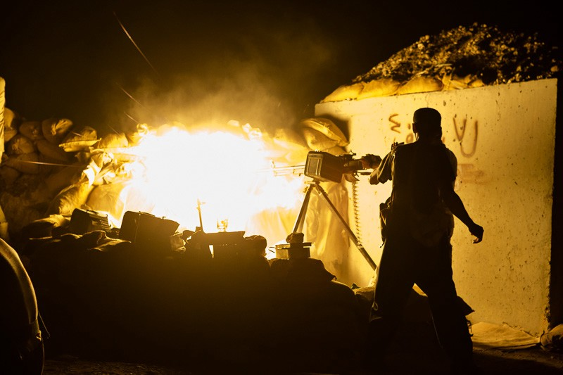 01/09/2015. Bashiqa, Iraq. A Kurdish peshmerga fighter fires a DShK heavy machine gun at ISIS vehicles moving near his unit's defensive position on Bashiqa Mountain, Iraq. Bashiqa Mountain, towering over the town of the same name, is now a heavily fortified front line. Kurdish peshmerga, having withdrawn to the mountain after the August 2014 ISIS offensive, now watch over Islamic State held territory from their sandbagged high-ground positions. Regular exchanges of fire take place between the Kurds and the Islamic militants with the occupied Iraqi city of Mosul forming the backdrop. The town of Bashiqa, a formerly mixed town that had a population of Yazidi, Kurd, Arab and Shabak, now lies empty apart from insurgents. Along with several other urban sprawls the town forms one of the gateways to Iraq's second largest city that will need to be dealt with should the Kurds be called to advance on Mosul.