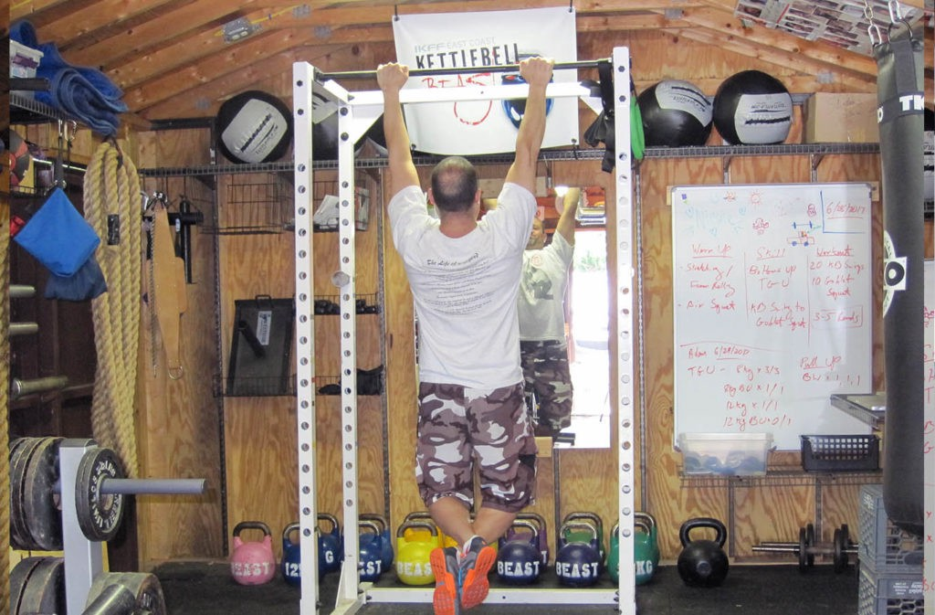 man hanging from the pull up bar in starting pull up position with feet crossed
