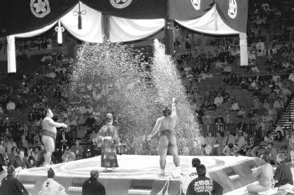 Sumo wrestlers scattering salt to purify the ring before a bout