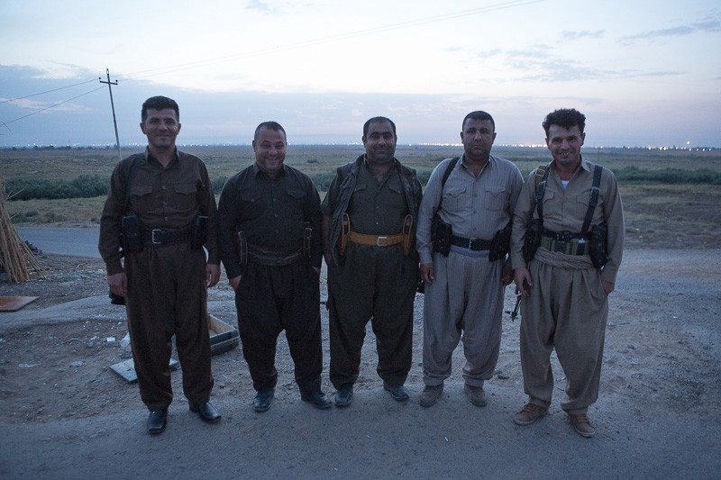 30/09/2015. Kirkuk, Iraq. Volunteer peshmerga: Zana (L), Aram (2L), Hardi (C), Sarwar (2R) and Hadji Fazer (R) stand for a group picture before taking part in a large offensive against ISIS held villages west of Kirkuk, Iraq. Supported by coalition airstrikes around 3500 peshmerga of the Patriotic Union of Kurdistan (PUK) and the Kurdistan Democratic Party (KDP) engaged in a large offensive to push Islamic State militants out of villages to the west of Kirkuk. During previous offensives ISIS fighters withdrew after sustained coalition air support, but this time in many places militants stayed and fought. The day would see the coalition conduct around 50 airstrikes helping the joint peshmerga force to advance to within a few kilometres of the ISIS stronghold of Hawija and re-take around 17 villages. Around 20 peshmerga lost their lives to improvised explosive devices left by the Islamic State, reports suggest that between 40 and 150 militants were killed.