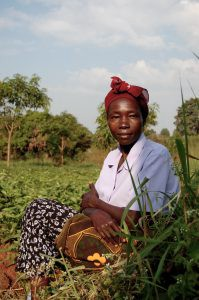 Ugandan violet farmer sitting in her field