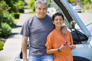 Hispanic father and son standing in front of car with hood up