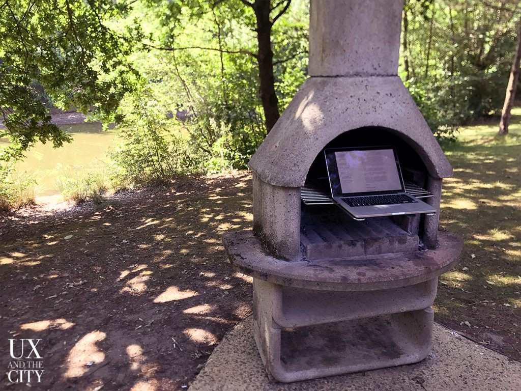 Laptop sitting on an outdoor grill in the middle of a forest.