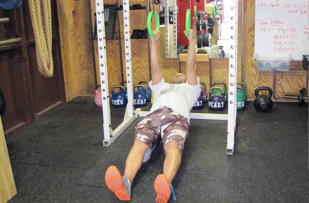 man hanging from rings with arms locked out in reverse plank position