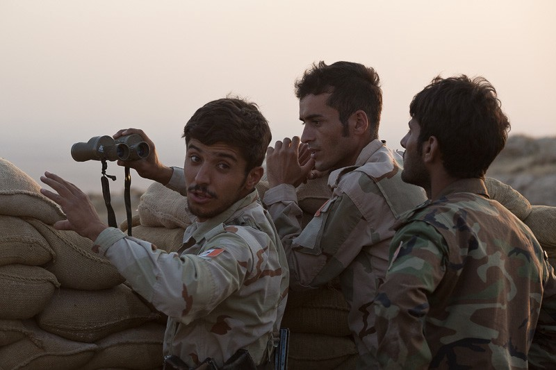 01/09/2015. Bashiqa, Iraq. Iranian Kurdish peshmerga fighters, belonging to 'PAK', a group who work alongside Iraqi Kurdish peshmerga, react to seeing ISIS vehicles moving in the Iraqi town of Bashiqa below their mountain top defensive position. Bashiqa Mountain, towering over the town of the same name, is now a heavily fortified front line. Kurdish peshmerga, having withdrawn to the mountain after the August 2014 ISIS offensive, now watch over Islamic State held territory from their sandbagged high-ground positions. Regular exchanges of fire take place between the Kurds and the Islamic militants with the occupied Iraqi city of Mosul forming the backdrop. The town of Bashiqa, a formerly mixed town that had a population of Yazidi, Kurd, Arab and Shabak, now lies empty apart from insurgents. Along with several other urban sprawls the town forms one of the gateways to Iraq's second largest city that will need to be dealt with should the Kurds be called to advance on Mosul.