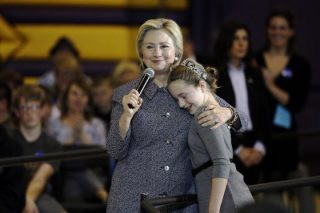 Democratic presidential candidate Hillary Clinton gets a hug from fifth-grader Hannah Tandy during a town hall meeting at Keota High School, Tuesday, Dec. 22, 2015, in Keota, Iowa. (AP Photo/Charlie Neibergall)