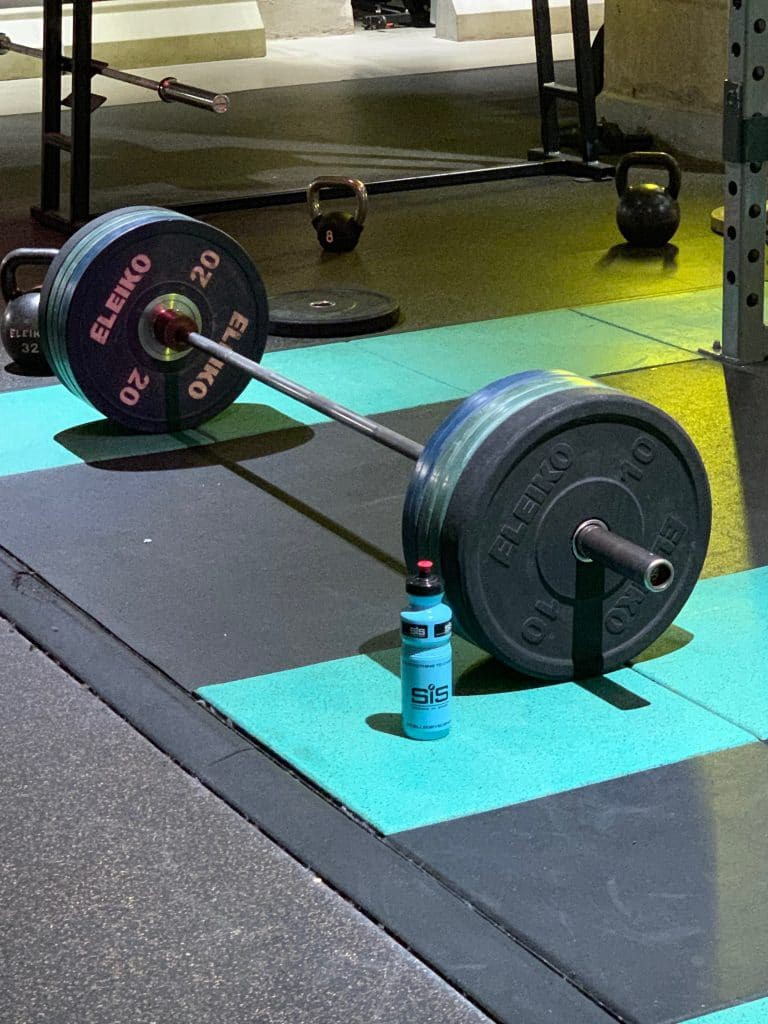 Iron discipline - deadlift bar loaded with heavy plates ready for tough lifting session