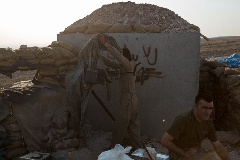 01/09/2015. Bashiqa, Iraq. As the sun goes down a Kurdish peshmerga fighter uncovers a DShK heavy machine gun at a defensive position on top of Bashiqa Mountain near Mosul, Iraq. Bashiqa Mountain, towering over the town of the same name, is now a heavily fortified front line. Kurdish peshmerga, having withdrawn to the mountain after the August 2014 ISIS offensive, now watch over Islamic State held territory from their sandbagged high-ground positions. Regular exchanges of fire take place between the Kurds and the Islamic militants with the occupied Iraqi city of Mosul forming the backdrop. The town of Bashiqa, a formerly mixed town that had a population of Yazidi, Kurd, Arab and Shabak, now lies empty apart from insurgents. Along with several other urban sprawls the town forms one of the gateways to Iraq's second largest city that will need to be dealt with should the Kurds be called to advance on Mosul.