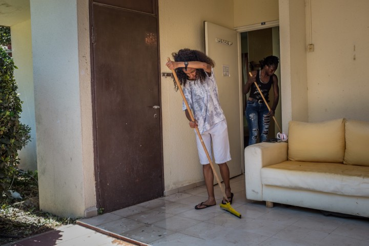 """Eritrean and South Sudanese asylum seekers and athletes Rahel (left) and Esteer (right) respectively, clean their shared bedroom in a training camp in northern Israel organized for the """"Alley Athletics"""" team they became part of after arriving in Israel as asylum seekers."""