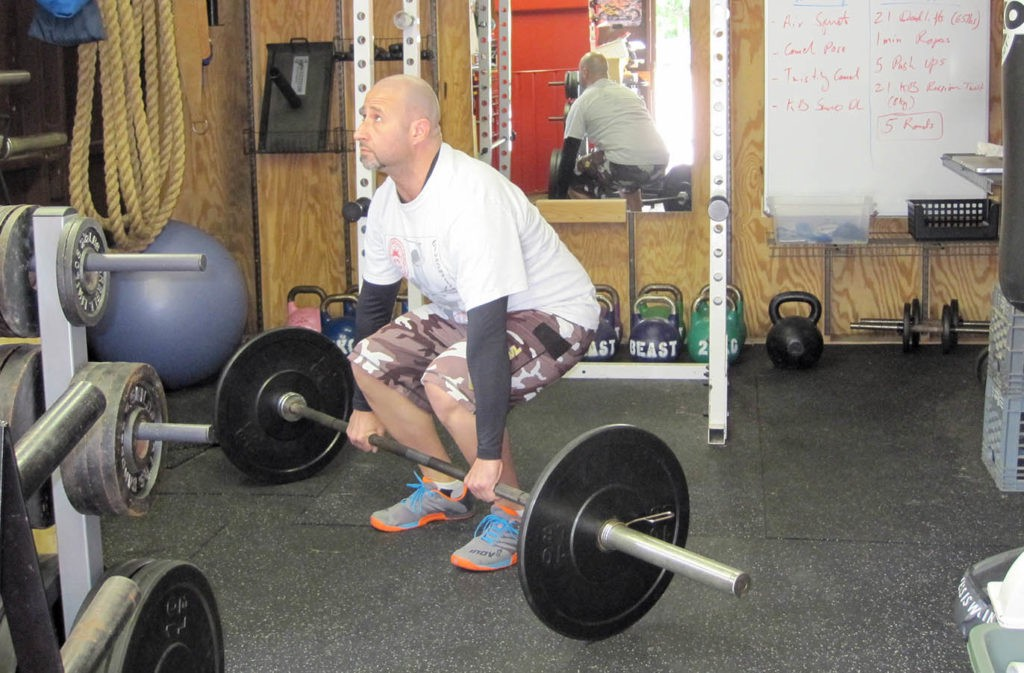 man starting to deadlift barbell with flat back