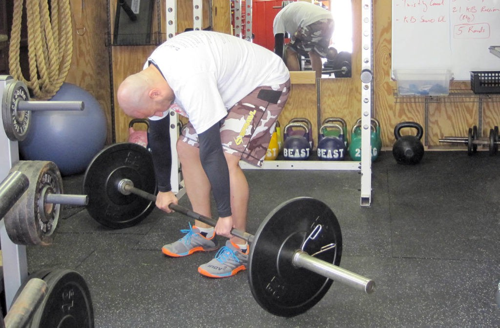 man starting to deadlift barbell with rounded back