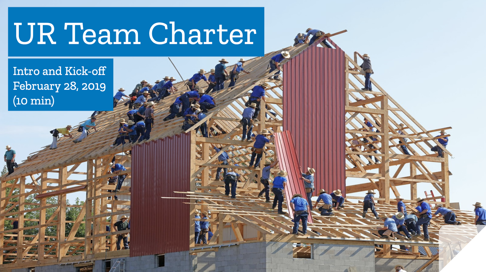 Photo of several dozen people building the frame of a large building