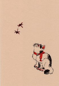 A cat watching two dragonflies flying