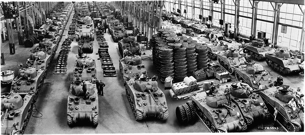 Above -- Sherman tank production. Photo via Detroit Public Library. At top -- German soldier with MG42. Photo via Wikipedia