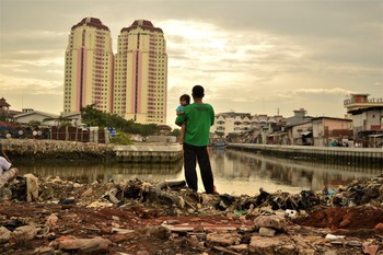 A father holds his daughter as he stands on a site from which local residents have recently been evicted to make way for new developments, close to luxury apartments in North Jakarta, Indonesia. Credit: Tiara Audina / Oxfam Feb 2017