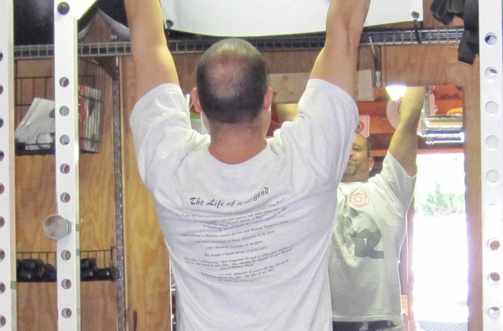 man in starting pull-up position with shoulders engaged