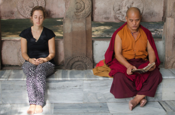 In this image it is the lay person on the left who appears to be meditating, and not the monk on the right, who is reading.(Ghosh/Tapasphotography/flickr).