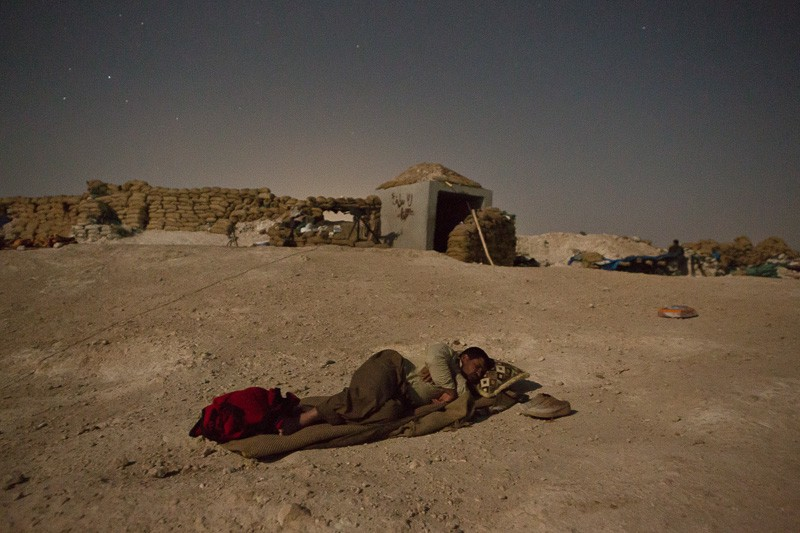 01/09/2015. Bashiqa, Iraq. A Kurdish peshmerga fighter takes advantage of a cool breeze by sleeping under the stars behind his unit's defensive position on Bashiqa Mountain, Iraq. Bashiqa Mountain, towering over the town of the same name, is now a heavily fortified front line. Kurdish peshmerga, having withdrawn to the mountain after the August 2014 ISIS offensive, now watch over Islamic State held territory from their sandbagged high-ground positions. Regular exchanges of fire take place between the Kurds and the Islamic militants with the occupied Iraqi city of Mosul forming the backdrop. The town of Bashiqa, a formerly mixed town that had a population of Yazidi, Kurd, Arab and Shabak, now lies empty apart from insurgents. Along with several other urban sprawls the town forms one of the gateways to Iraq's second largest city that will need to be dealt with should the Kurds be called to advance on Mosul.