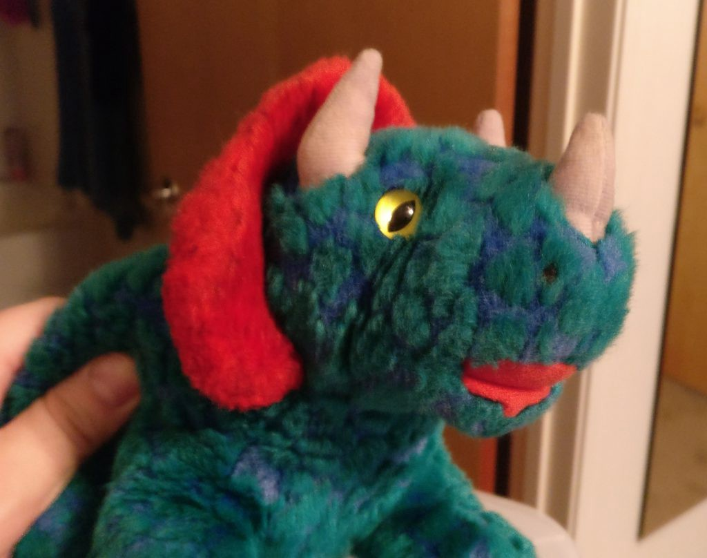My stuffed dinosaur Harold, a green, blue, and red stuffed animal. I discovered him after digging through some things and took this picture to show a friend.