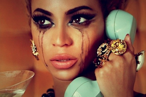 A still of Beyoncé with mascara running down her cheeks as if she's been crying. She's holding a light blue handset to her ear.
