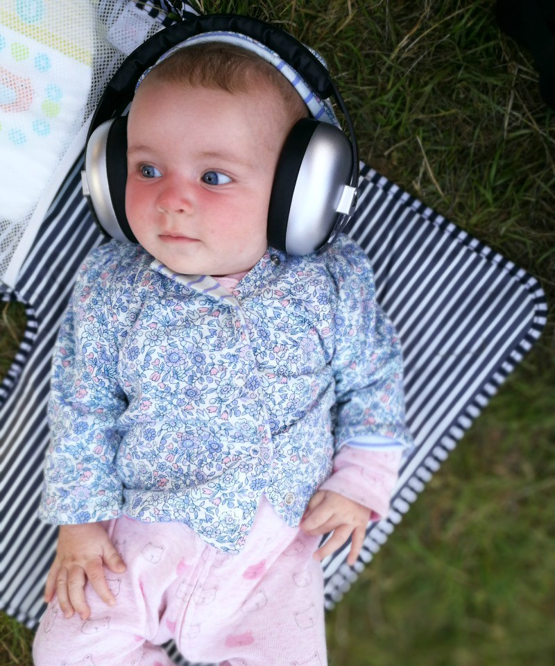 festival packing list newborn - cute baby with ear defenders on