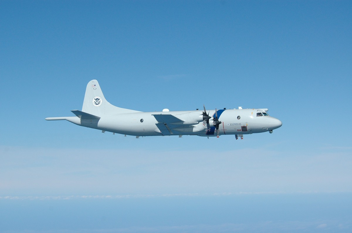 Above - a P-3 Long Range Tracker patrol plane. Customs and Border Protection photo. At top - Coast Guardsmen on top of the narco sub. Coast Guard capture.