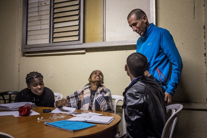 """Eritrean asylum seeker and athlete Rahel Gebretsadik (center) studies and helps team members Chinenye Ohanenye (left) and Eshetu Werku (right) with homework with the help of the team's Medium and Long-range distance running coach Yuval Carmi (back) during an athletic sports camp in northern Israel organized for their """"Alley Athletics"""" team."""