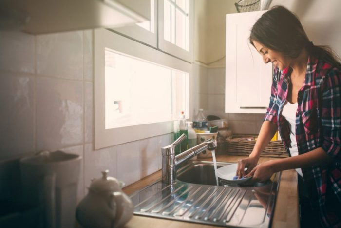 Woman standing and washing dishes