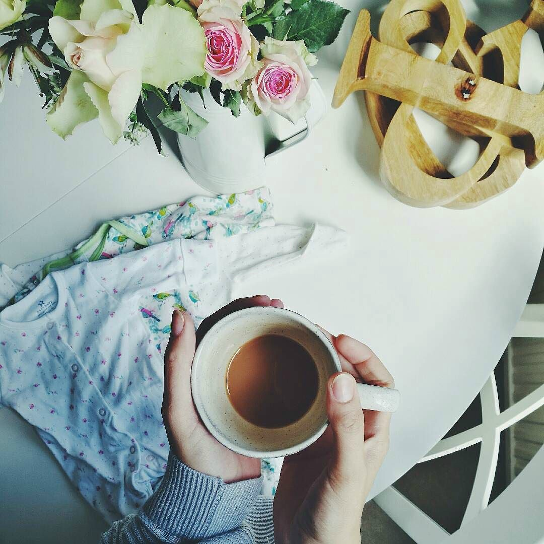 writers block - womans hands holding tea above flatlay with baby clothes