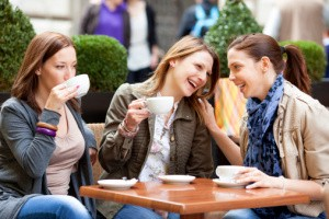 Young Women Having Fun Drinking Coffee Outdoors.