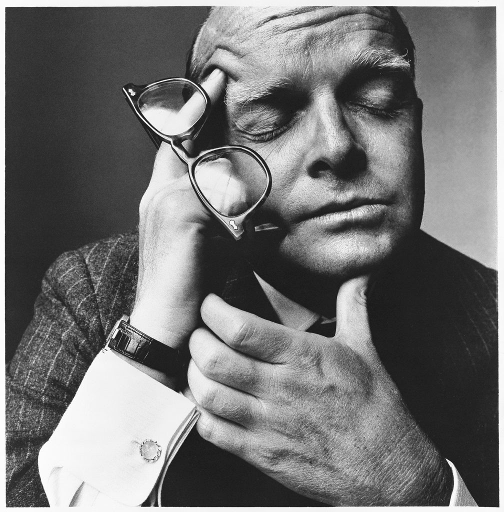 Truman Capote holding a glasses