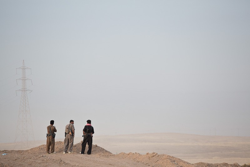 30/09/2015. Kirkuk, Iraq. The Kurdish peshmerga fighters look in to no-man's land from a Kurdish front line position as they wait for the start of a large offensive against Islamic State held villages to the west of Kirkuk, Iraq. Supported by coalition airstrikes around 3500 peshmerga of the Patriotic Union of Kurdistan (PUK) and the Kurdistan Democratic Party (KDP) engaged in a large offensive to push Islamic State militants out of villages to the west of Kirkuk. During previous offensives ISIS fighters withdrew after sustained coalition air support, but this time in many places militants stayed and fought. The day would see the coalition conduct around 50 airstrikes helping the joint peshmerga force to advance to within a few kilometres of the ISIS stronghold of Hawija and re-take around 17 villages. Around 20 peshmerga lost their lives to improvised explosive devices left by the Islamic State, reports suggest that between 40 and 150 militants were killed.