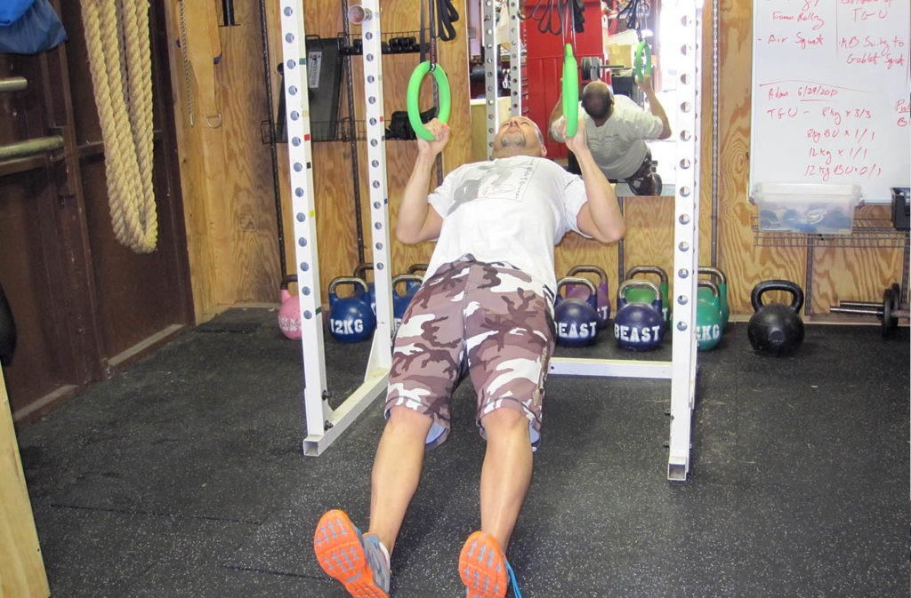 man hanging from rings in reverse plank position arms bent in top of ring row position