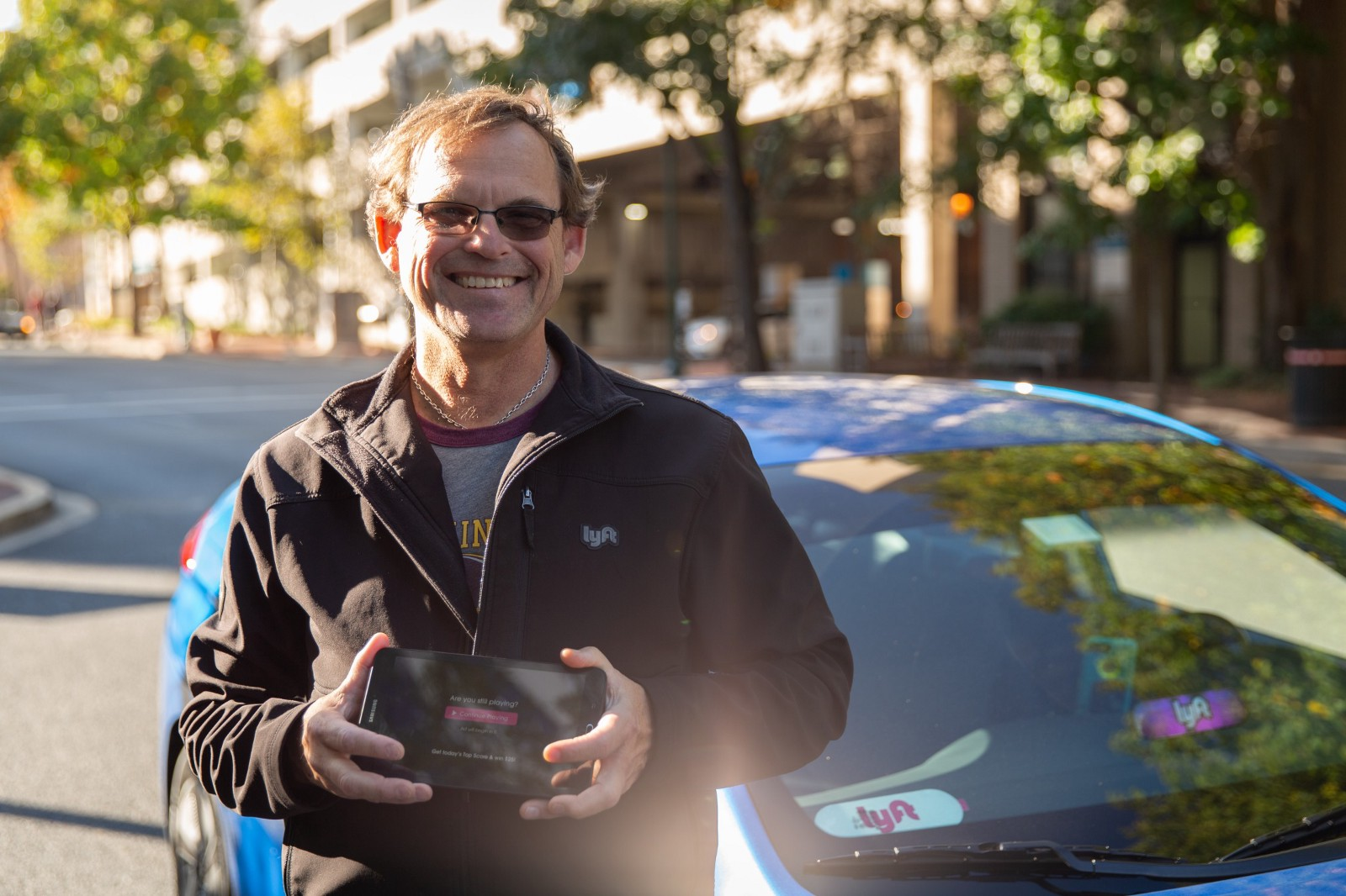 Dave Kremnitzer, a rideshare driver, stands with his Octopus rideshare entertainment tablet in front of his vehicle.
