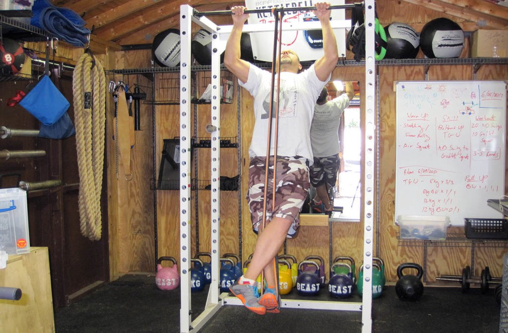 man doing pull up on pull up rig with assistance of resistance bands