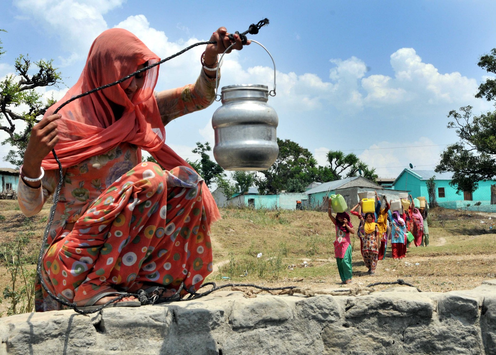 JAMMU, INDIA - APRIL 27: A lady collecting drinking water from an almost dried up well as other coming to collect at Padal village of Samba district, around 40 kilometer from Jammu, on April 27, 2016 in Jammu, India. According to reports, 10 villages in Samba district of Jammu and Kashmir are drought-affected. The drought has been ongoing for the past two months in the region, forcing women and children to walk miles to fetch water. (Photo by Nitin Kanotra/Hindustan Times via Getty Images)
